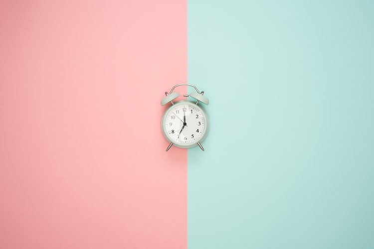 an alarm clock on a blue and pink background