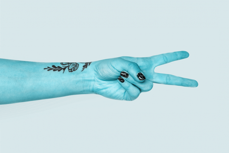 a hand with the 2nd and 3rd finger pointed outwards. The hand is blue in colour
