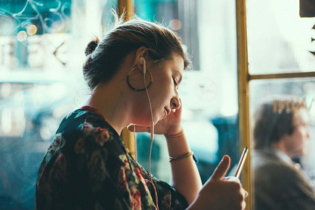 a lady wearing a ponytail hairstyle earphones in her ears, holding a looking at her phone